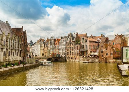 Ghent, Belgium - April 12, 2016: Old houses along canal and boat with tourists in popular touristic destination Ghent, Belgium.