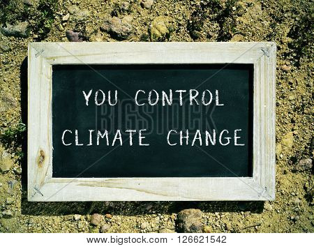 closeup of a wooden framed chalkboard with the text you control climate change
