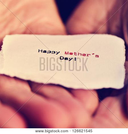 closeup of a piece of paper with the text happy mothers day in the hands of an adult person