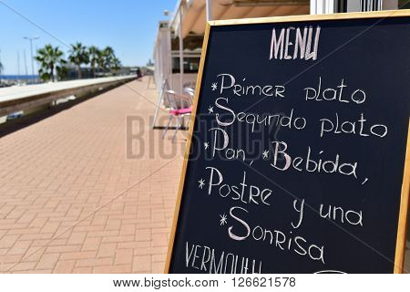 closeup of the chalkboard of a restaurant in a coastal city in Spain, with a generic menu including a starter, a main course, bread, beverage, dessert and a smile, written in spanish