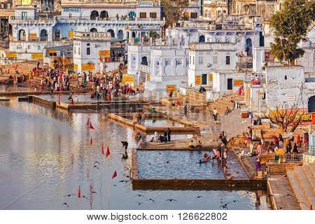 PUSHKAR, INDIA - NOVEMBER 20, 2012: Hindu devotees pilgrims bathing in sacred Puskhar lake (Sagar) on ghats of  Pushkar, Rajasthan. Pushkar is holy city for Hinduists and famous for many Hindu temples