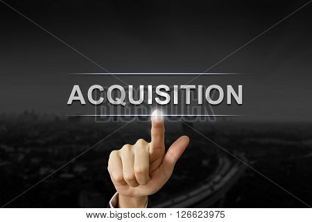 business hand clicking acquisition button on black blurred background