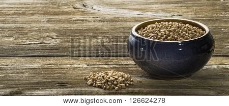 Clay saucepan with buckwheat groats on wooden background
