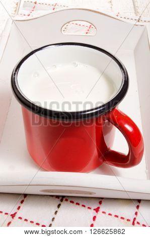 warm milk in a red enamel mug on a wooden serving tray
