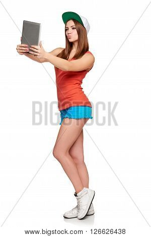 Full length sporty female with digital tablet capturing image or videochat blowing a kiss, over white