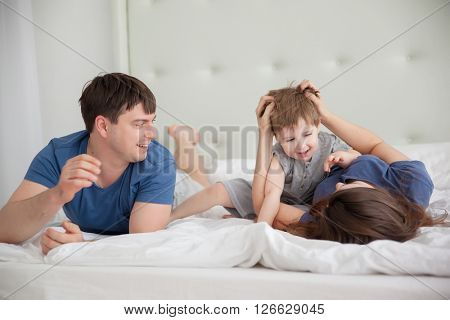 Family portrait of three people On Parents Bed Wearing Pajamas