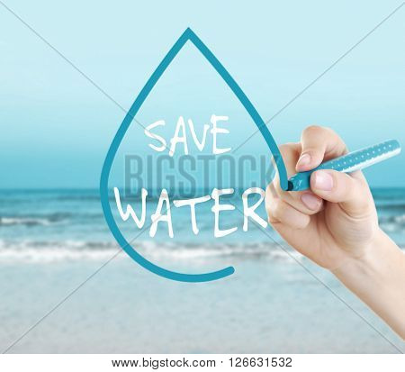 Female hand with felt-tip pen and Save Water text in drop frame on sea background
