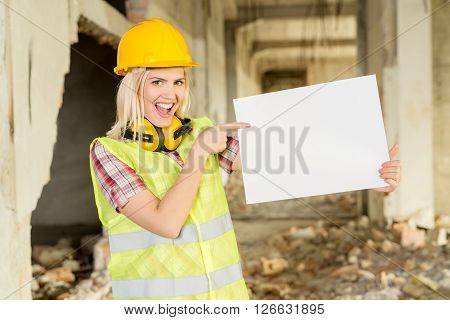 Beautiful young female construction architects in building damaged in the disaster. She is point to a blank white board and smiling looking at camera.