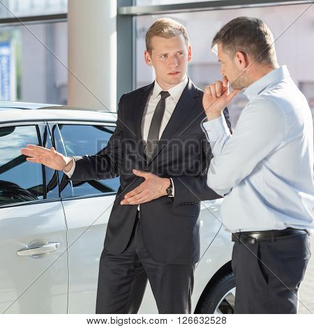 Car dealer showing a new vehicle, square ** Note: Soft Focus at 100%, best at smaller sizes