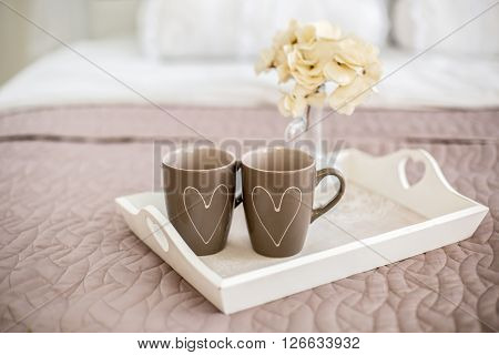 Two cups with painted hearts.Blank heart shaped card and flowers with breakfast served in bed. Extreme shallow depth of field with selective focus on heart.