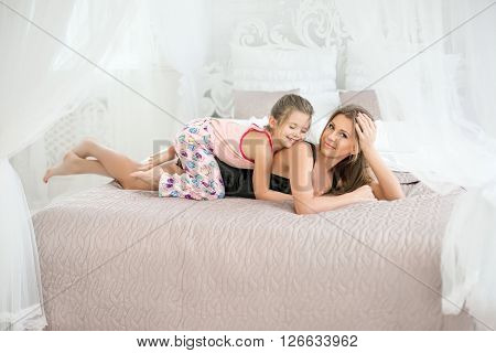 Mom And Daughter In Bed. The Girl On The Back Of At Mum.