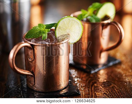 two Moscow mules in copper cup with lime and mint garnish