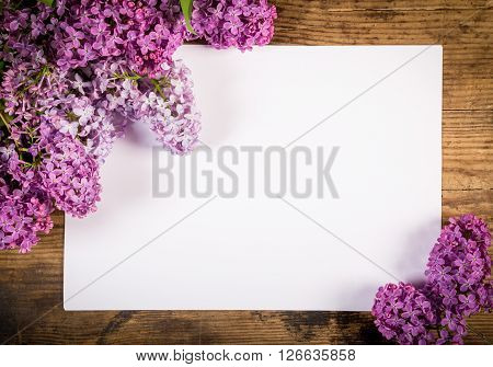 Bunch of lilac on brown wood old table with blank paper page, empty space for text