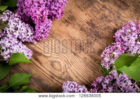 Bunch of lilac flowers on brown wood diagonal texture with empty space for text