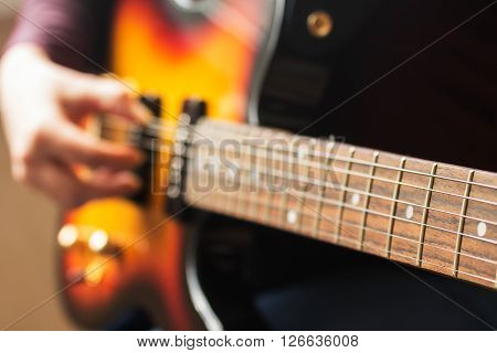 Woman's hands playing electric guitar close up with very shallow depth of field soft focus