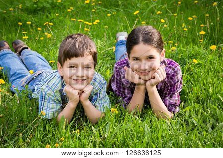 Two smiling kids lying together on green grass meadow