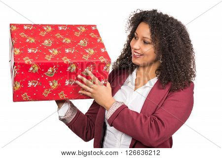 Cut out image of a young woman who is looking to a christmas gift while she is holding it.
