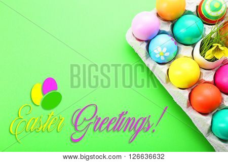 Easter greeting card. Colorful eggs in tray on green background