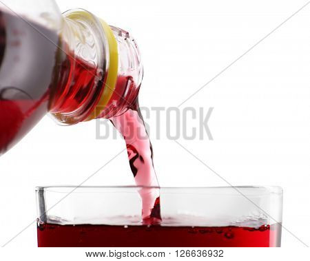 Pouring cherry soda from plastic bottle into glass on grey background