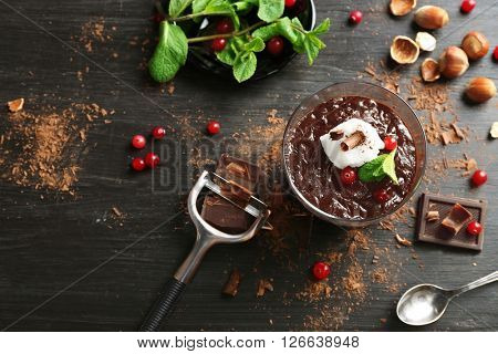 Glass cup of chocolate dessert with cranberries, fresh mint and frothed milk on black wooden table