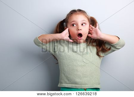 Surprising Kid Girl With Long Hair With Opened Mouth And Hand Near Face Looking On Blue Copy Space B
