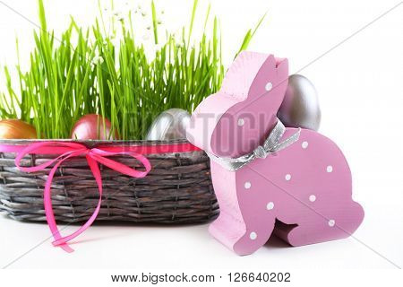 Multicoloured Easter eggs in a wicker bowl with grass isolated on white