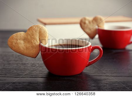 Heart shape cookie on cup of coffee on wooden table closeup