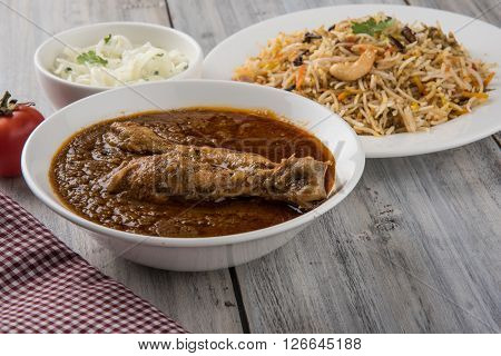 The most popular reddish chicken curry in the UK, india, pakistan, asia, chicken tikka masala, here served in bowl, accompanied by pilau rice and chapatis.