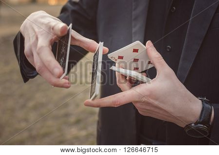 Hands of man doing a magic card trick in the park
