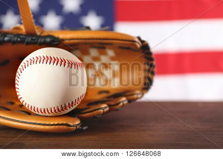Baseball in glove in front of American state flag