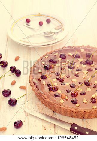Sweet chocolate tart cake with dark cherries.Selective focus on the chocolate tart