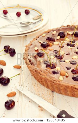Sweet chocolate tart cake with dark cherries.Selective focus on the front part of tart