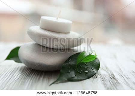 Spa stones with green leaves and candle on white wooden table