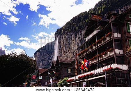 LAUTERBRUNNEN, SWITZERLAND - AUGUST 27, 2014: Hotel Oberland and Other Buildings with Staubbach Falls in the Background on August 27, 2014 in Tourist Town of Lauterbrunnen in Lauterbrunnen Valley, Jungfrau Region, Switzerland.