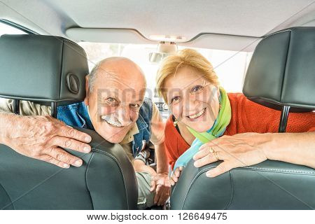 Happy senior couple ready for driving car on journey trip - Concept of joyful active elderly with retired man and woman enjoying their best years - Modern mature travel lifestyle during retirement