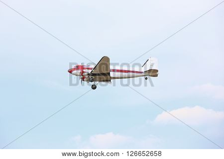 Red-white airplane flying through blue sky with clouds