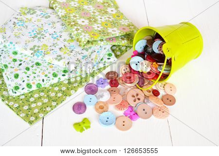 Pieces of green cloth and colorful buttons in a decorative green bucket