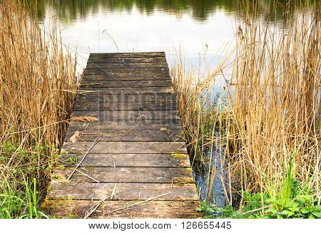 Photo closeup of a wooden pier on the lake. Clearly visible boards and blemishes on wood. Horizontal view.