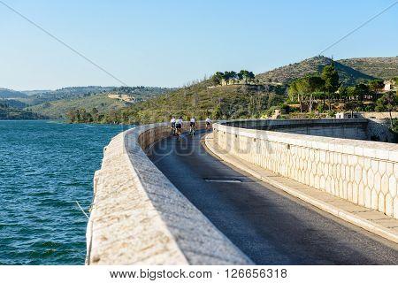 MARATHON GREECE- JUNE 6 2012: Cyclists crossing the Marathon dam