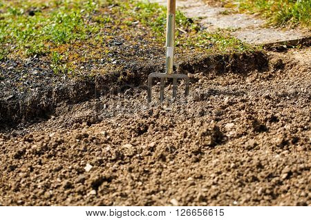 Garden fork pitched in soil symbolizing garden work gardening and planting preparation. Housework self-supply food production having a break from work concept.