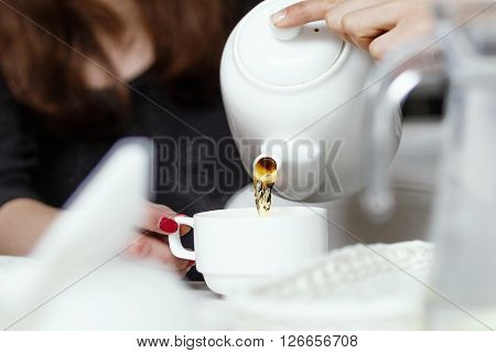 side view of a girls pouring tea, pouring tea from teapot into a cup close-up
