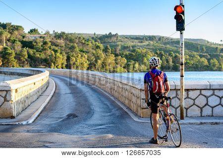 MARATHON GREECE- JUNE 6 2012: Cyclist waiting at the traffic light to cross the Marathon dam
