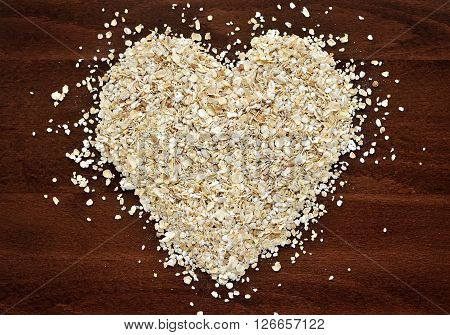 Heart Shape Made From Oat Flakes On Dark Wooden Table
