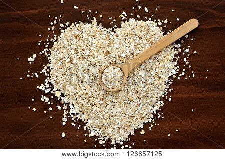 Heart Shape Made From Oat Flakes With Spoon On Dark Wooden Table
