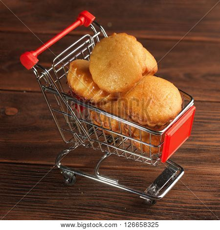 Christmas muffins in trolley in a supermarket on wooden background