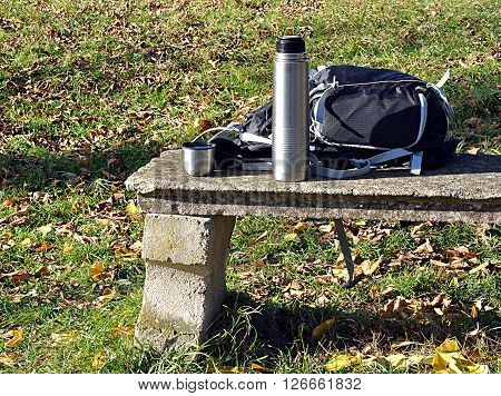 backpack and a thermos on a bench in nature