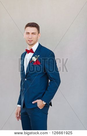 Portait of a young handsome man in suite. Close up of a gorgeous guy on gray background