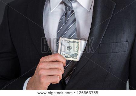 Businessman Putting Bribe In Suit Pocket