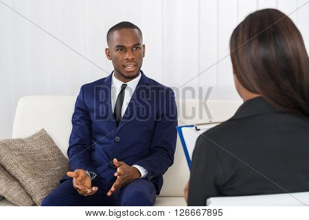 Young Man Talking With Psychologist About His Problems