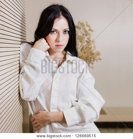 Half length portrait of young sexy girl in white shirt standing and leaning on bedroom wall, boudoir concept, soft light filter